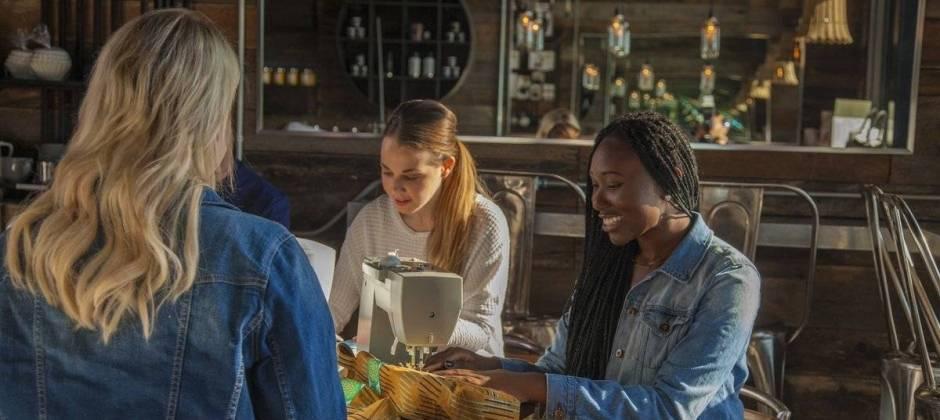 Singer naaimachine met jonge dames in café